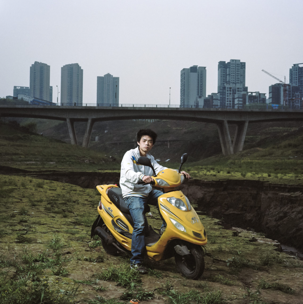 Patrick Wack, Chongqing 02, 2013 This image of a young Chinese boy on a scooter was made in the spring of 2013 in the city of Chongqing. I travelled twice two weeks that year to this incredible metropolis as part of my China Portraits project. I had been there for the first time in 2010 and had loved the mix of chaotic urbanism, science-fiction atmosphere and gigantism. I made this portrait on the banks of the Jialing River in downtown Chongqing. We were walking on this moon like type of earth and a bit further down we could see this huge rift through which sewage was flowing. This boy came driving by on his flashy yellow scooter and I ran after him to try and get his portrait among this apocalyptic environment. He seemed to think that was a perfectly normal place to spend some time.