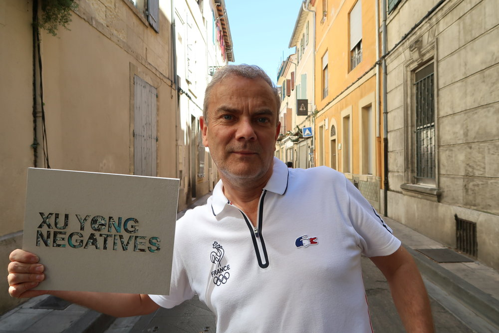 "Pierre Bessard holding his Xu Yong's ""Negatives"" monograph published by his eponymous publishing house in 2017"