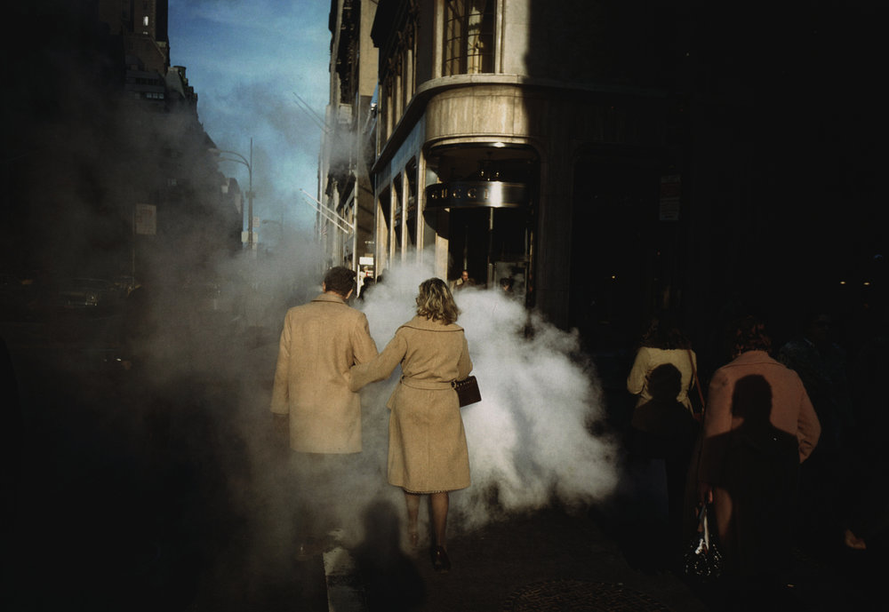 Joel Meyerowitz,  Couple au manteau camel sur Street Steam, New York , 1975. Avec l'aimable autorisation de l'artiste et de la Howard Greenberg Gallery /  Camel Coat Couple in Street Steam, New York City , 1975. Courtesy of the artist and Howard Greenberg Gallery.