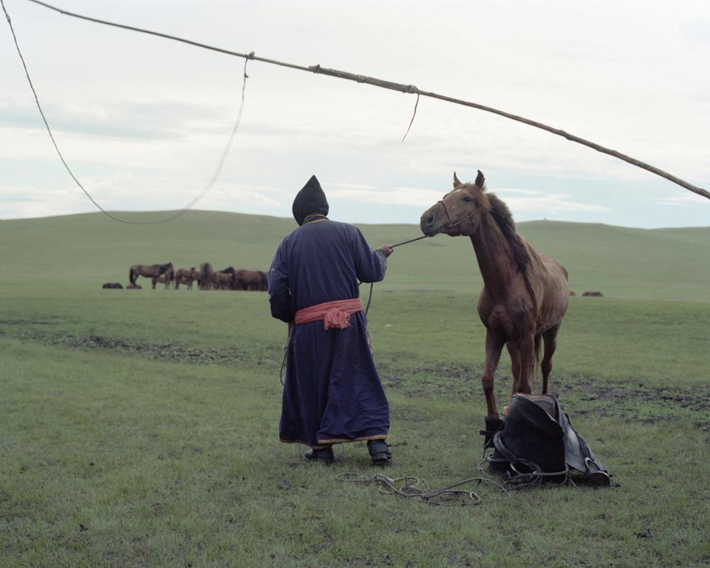 A Mongolian man is leading a horse,Inner Mongolia,2011-li-wei-photography-of-china.jpg
