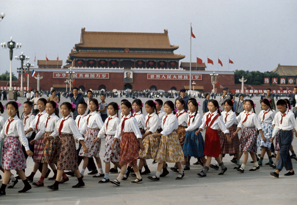 "Bruno Barbey, 'Tiananmen Square. School girls prepare for the reception of French president Georges Pompidou. In the background: Mao portrait and slogans ""Long live the People's Republic of China. Long live the Union of the people of the world.""' Beijing, China, 1973. © Bruno Barbey/Magnum Photos"