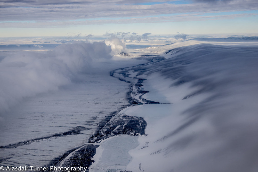 Clouds fall over Minna Bluffs, Antarctica.  Shot from a Twin Otter.