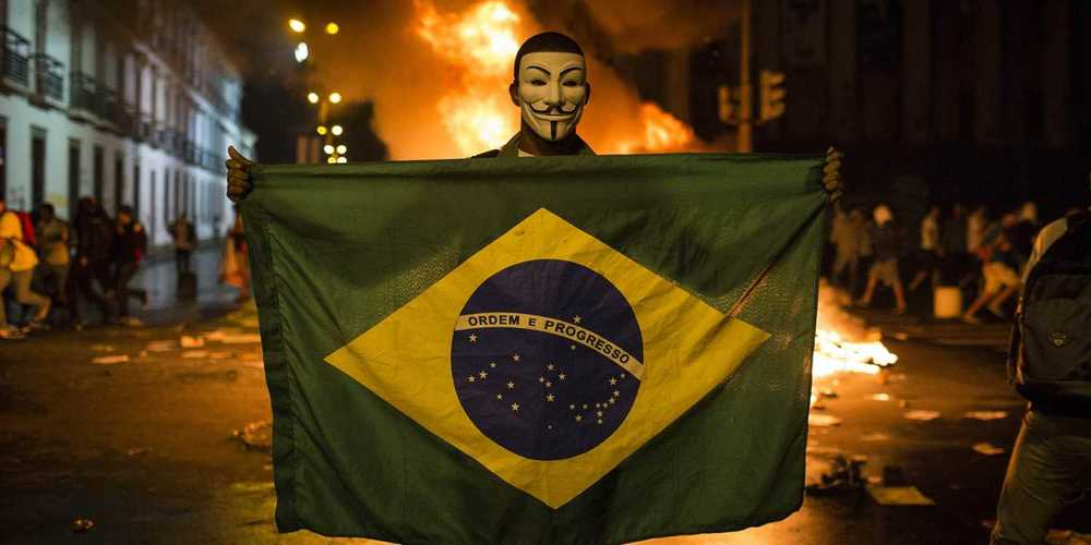 Protestor from Brazil masked in the infamous V for Vendetta mask holds up Brazilian Flag  on the streets - Getty Images (c)