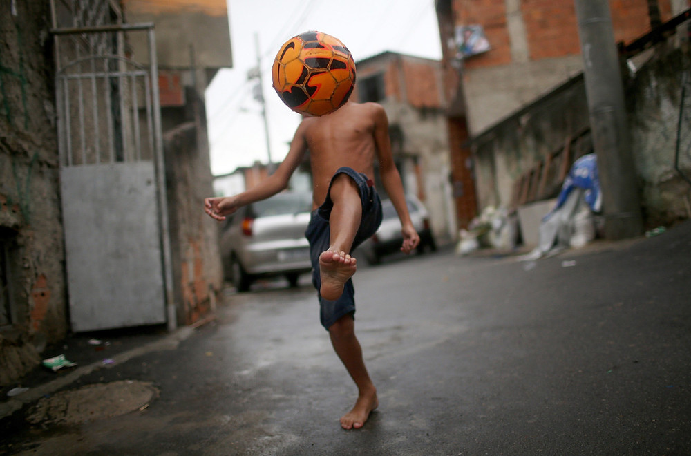 Youth plays with a football in the Favelas of Brazil - Getty Images Brazil (c)