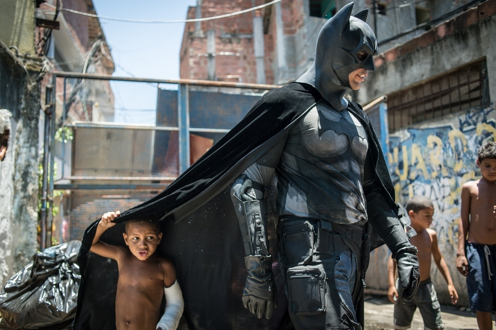 An anti-government protester dressed as Batman walks among the people of Rio De Janerio, who are protesting the demolition of their homes to make way for the FIFA World Cup. Picture taken in the Favela do Metro slum in Rio, an area near the Maracana stadium playing host to the 2014 games.  Getty images Brazil (c)