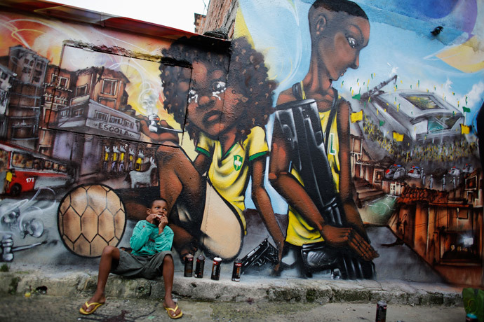 Ryan, 9, eats in front of graffiti painted by members of OPNI, in reference to the 2014 World Cup, in the Vila Flavia slum of Sao Paulo May 28, 2014. (Reuters / Nacho Doce)