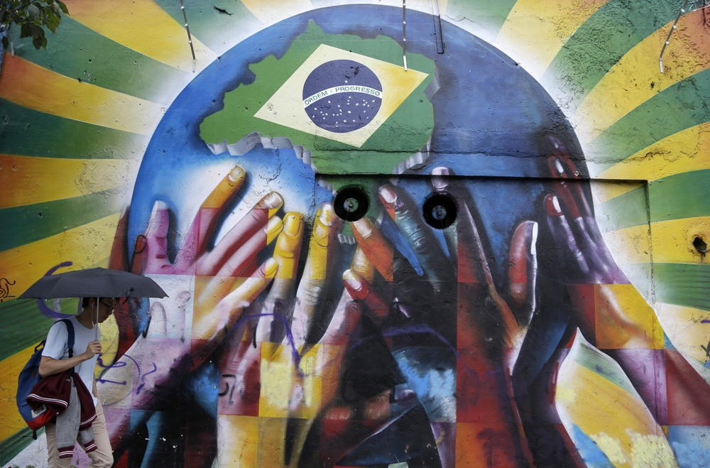 Defining a global cup - street art depicting hands holding the world with the Brazilian Flag in Sao Paolo. Associated Press (c) 2014