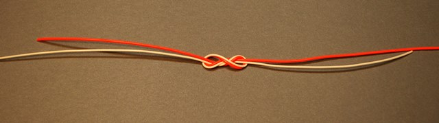 A double Surgeon's Knot before it's drawn tight. The orange line represents the leader (4X tippet material in this example) also known as the parent material. The white line represents the tippet material (5X tippet material in this example) being tied to the leader. Note that the tag end of 4X material lies alongside the tippet tippet material.