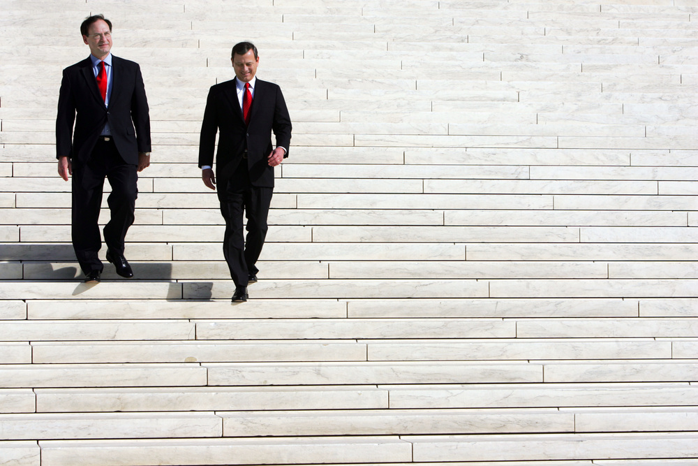 Supreme Court Justices John Roberts and Samuel Alito talk on the front steps of the Supreme Court.