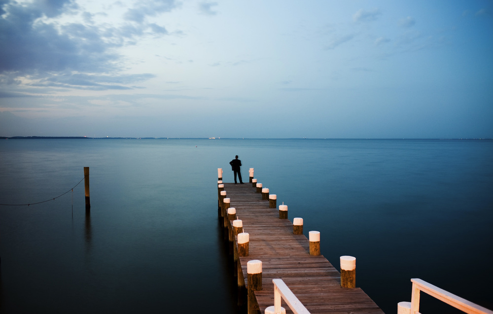 A man stands on a dock at dusk in Pasadena, Maryland.