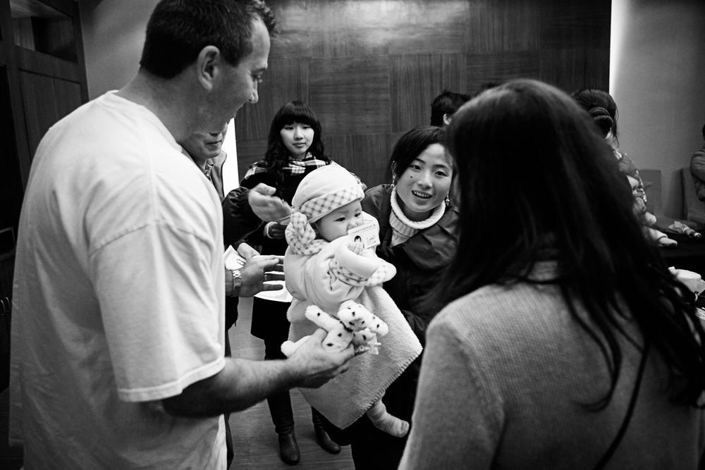 An adoption agency staff members hands Karen and Bob their baby daughter, Kailee.