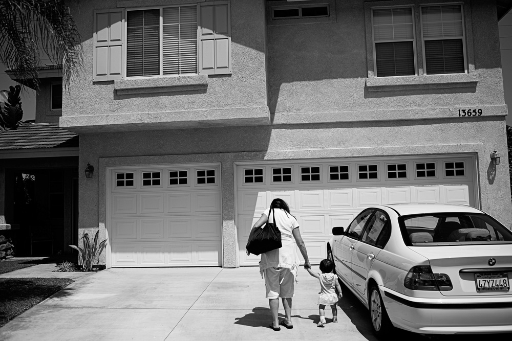Karen holds Kailee's hand as they walk to their house after a day of shopping and visiting the playground, in Orange County, California.