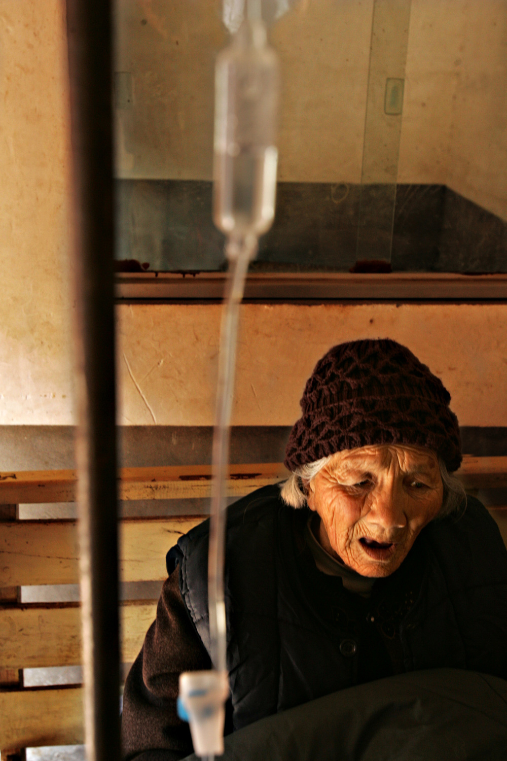 A woman is treated for a stomach ailment using an IV drip in Sunying Village in Shenqiu County. The local caregiver suspects she has stomach cancer, but she is unable to afford medical care.