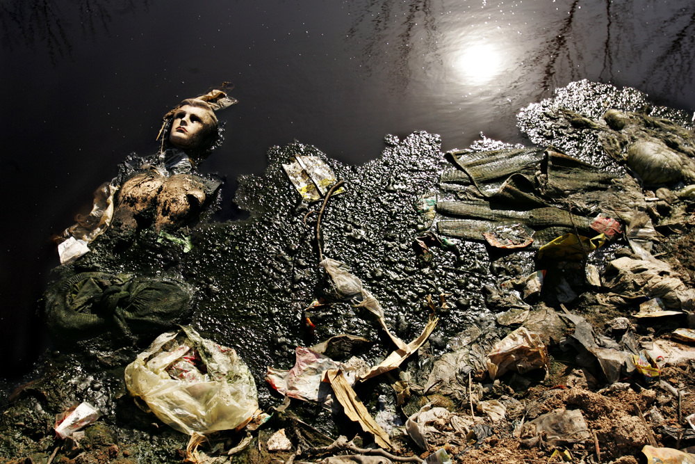 A mannequin floats in the water at a secret dumping site of Lianhua MSG Factory. The water coming from the factory is nearly black. Upstream is a pharmaceutical company and a leather tannery, both owned by Lianhua, who also dump their wastewater into the river.