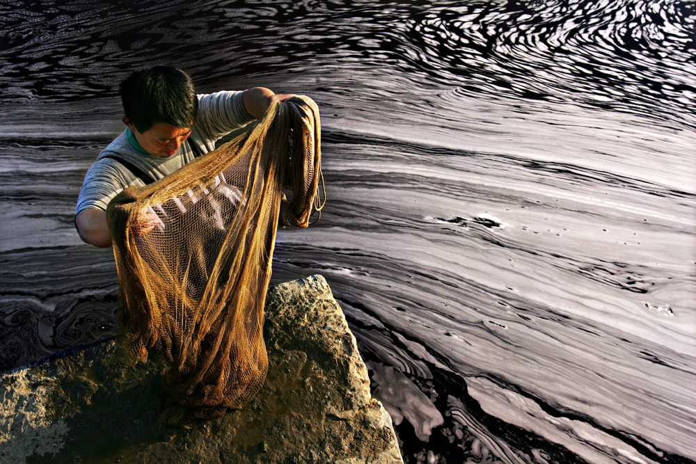 A fisherman examines his net for fish after casting it in the polluted waters of a river in Shenqiu County. After an hour's work, he was able to catch ten small bait fish with blisters on their bodies.