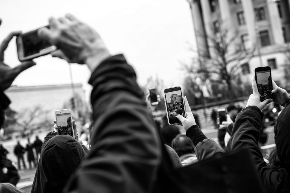 Attendees try to capture a glimpse of the President-elect arriving along Pennsylvania Avenue prior to the Presidential Inauguration in Washington, DC on January 20, 2017.