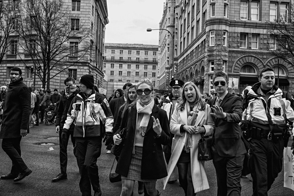 A group of people staying at the Trump Hotel are escorted past protesters after President Trump's executive order banning people from seven countries from entering the United States, on January 29, 2017.