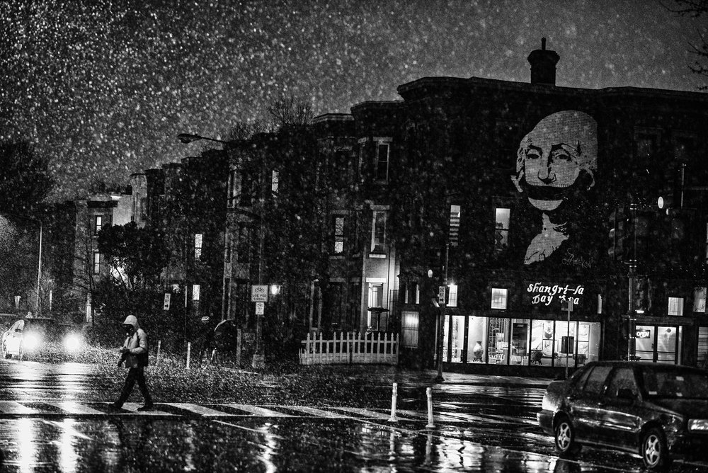 A mural of President George Washington with a gag over his mouth, during a snowstorm in Washington, DC, on March 13, 2017.