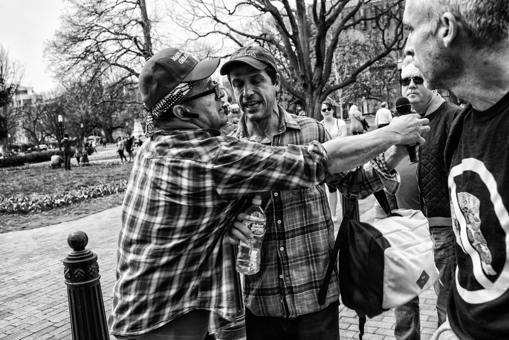 The driver of a pro-Trump trailer reaches for his microphone after it was taken from him by an attendee of the nearby Pizzagate demonstration in Lafayette Square on March 25, 2017.