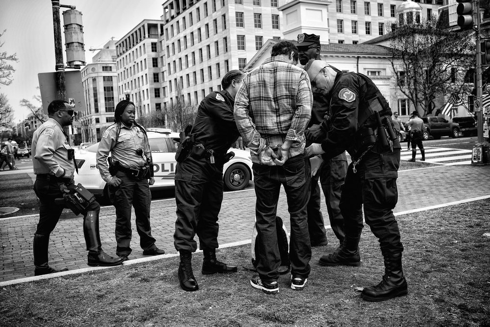 An attendee of the Pizzagate demonstration is arrested after taking a microphone from a Trump supporter in Lafayette Square on March 25, 2017.
