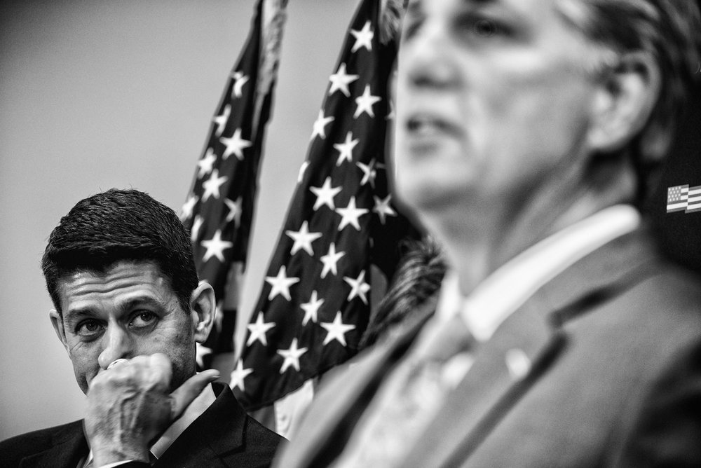 House Speaker Paul Ryan listens to House Majority Leader Kevin McCarthy speak to the media during a briefing after attending a closed House Republican conference on March 28, 2017