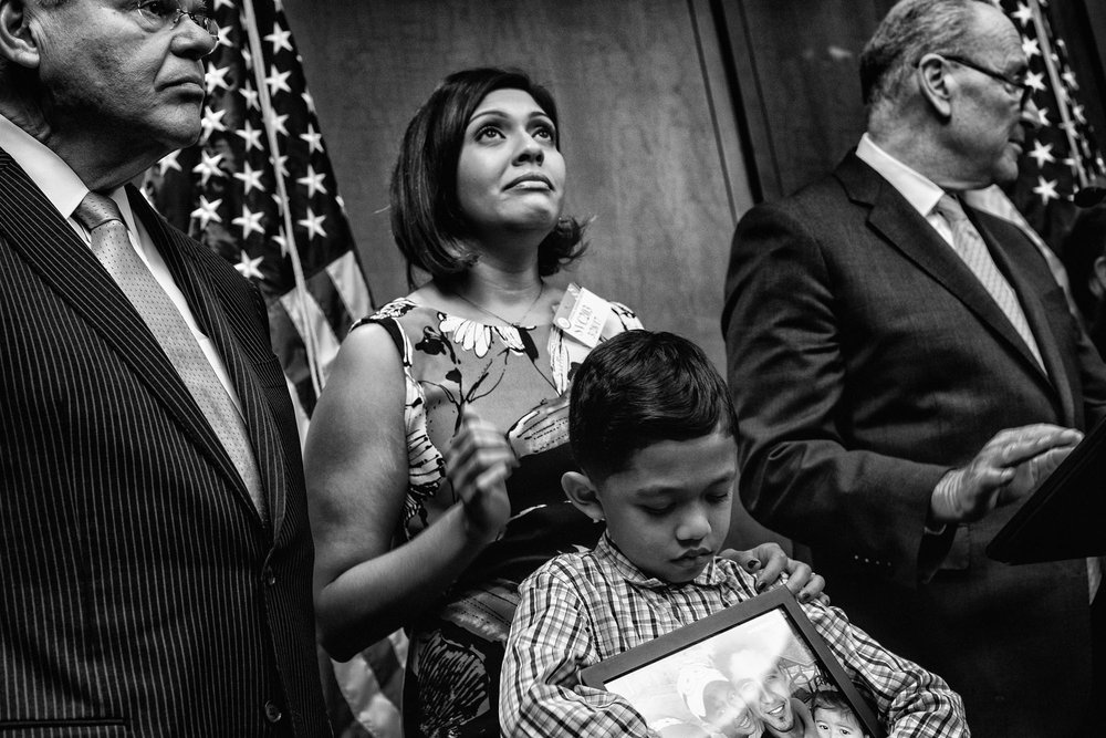 Walter Escobar holds a photograph of his family while standing with his mother, Rose during a news conference with La Raza and Senators Menendez and Schumer.  Walter's father, Jose, had been deported to El Salvador despite having no criminal record.