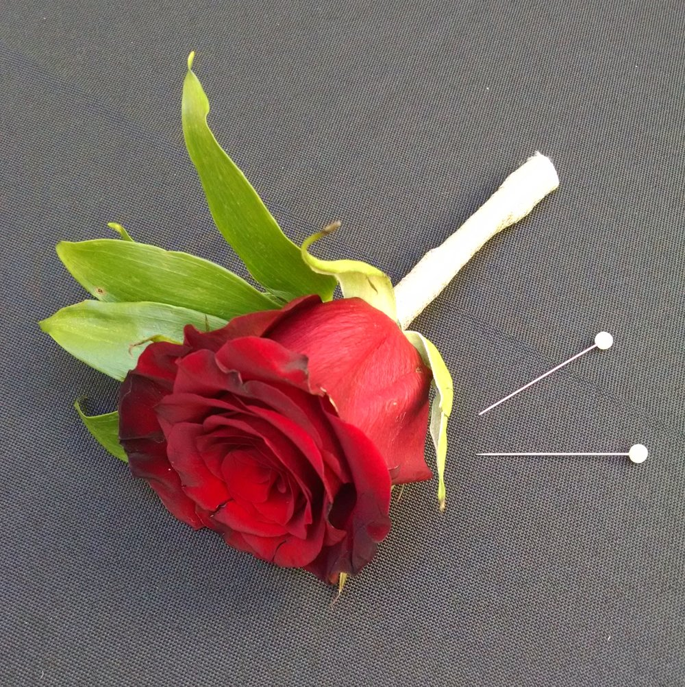 You need a boutonniere and two pins.  Yes, two pins!