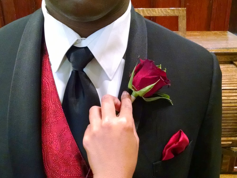 The boutonniere goes on the left lapel, which is the one on the right if you are doing the pinning.