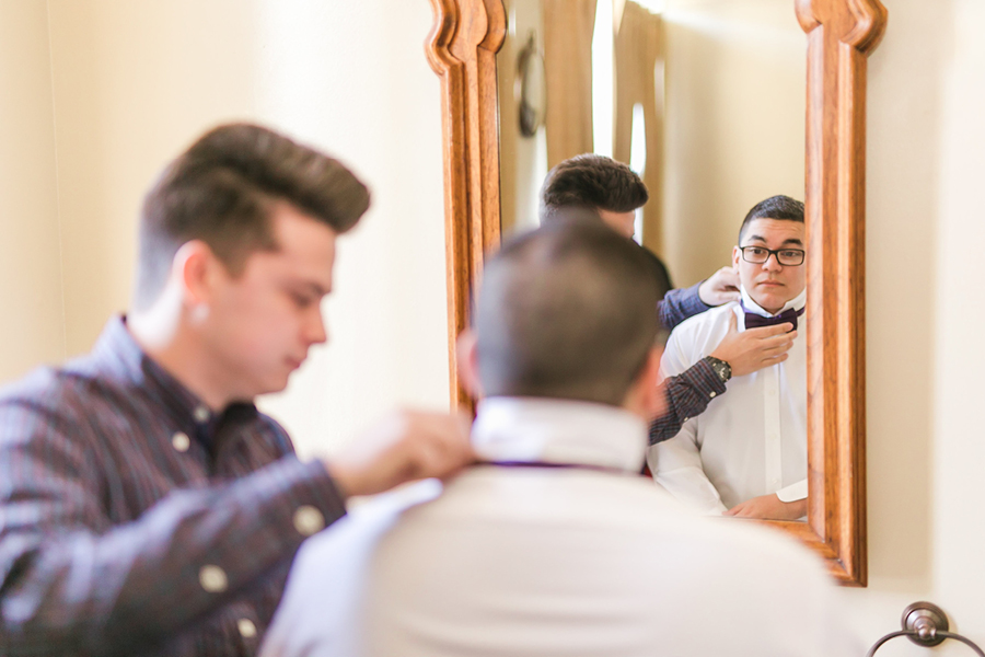 Groom getting ready, groomsman tying a tie, Events on 6th, Photo by Lloyd Photography