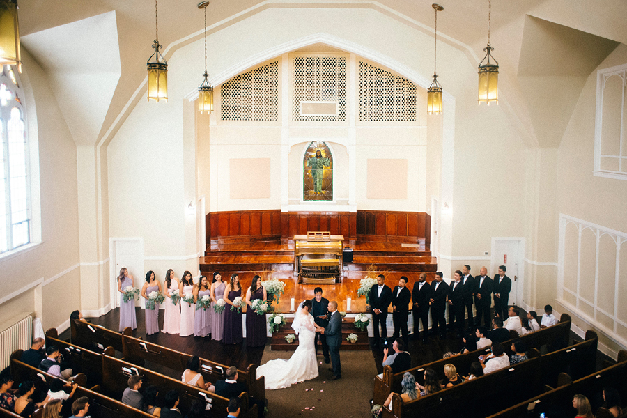 Church wedding with bride and groom, bridesmaids and groomsmen, high ceiling, stained glass, historic church, Seattle wedding venue, Events on 6th, Photo by Christina Klas