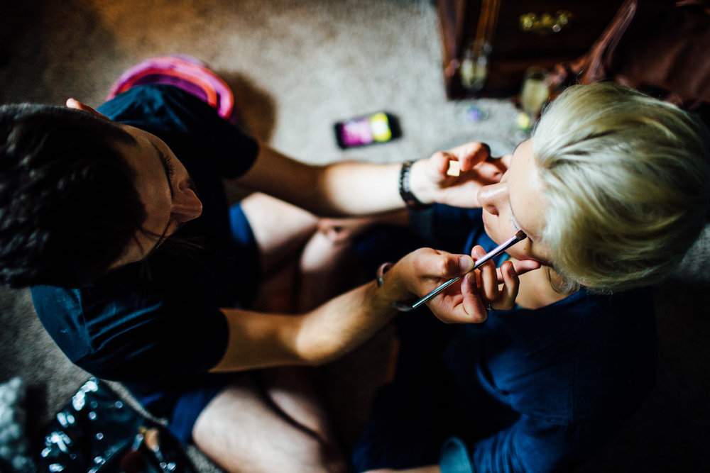 bride gets makeup done by make up artist
