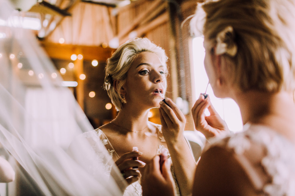 bride puts on lip gloss in mirror