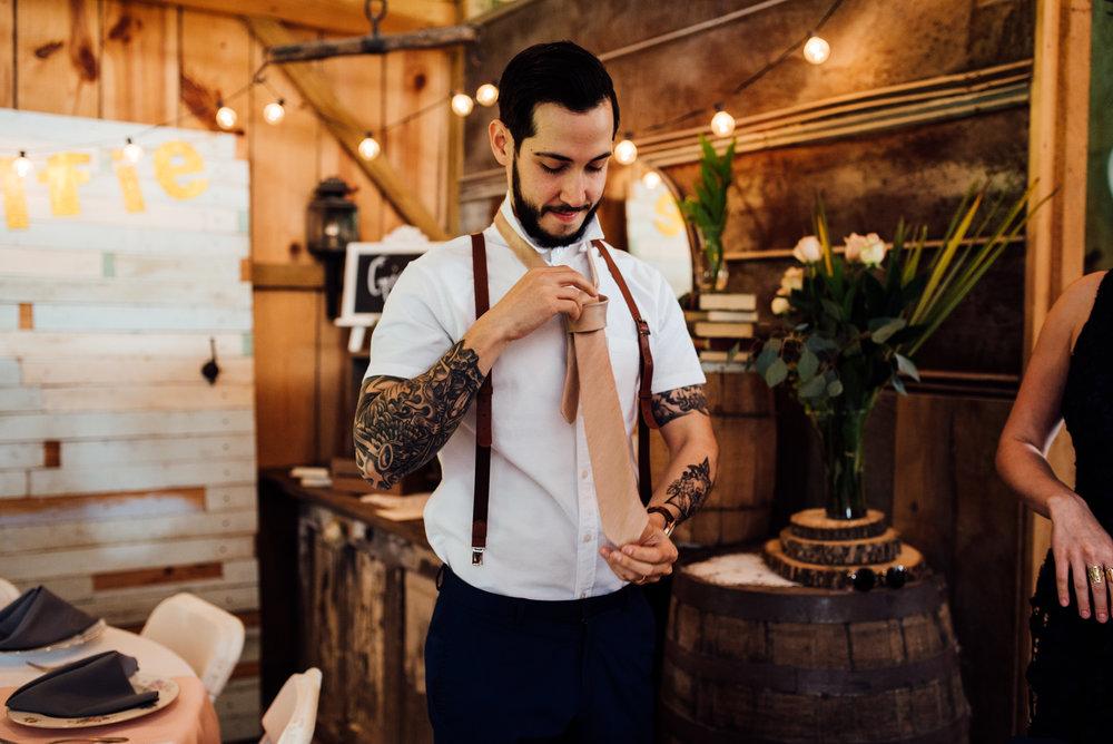 tattooed groom puts on tie