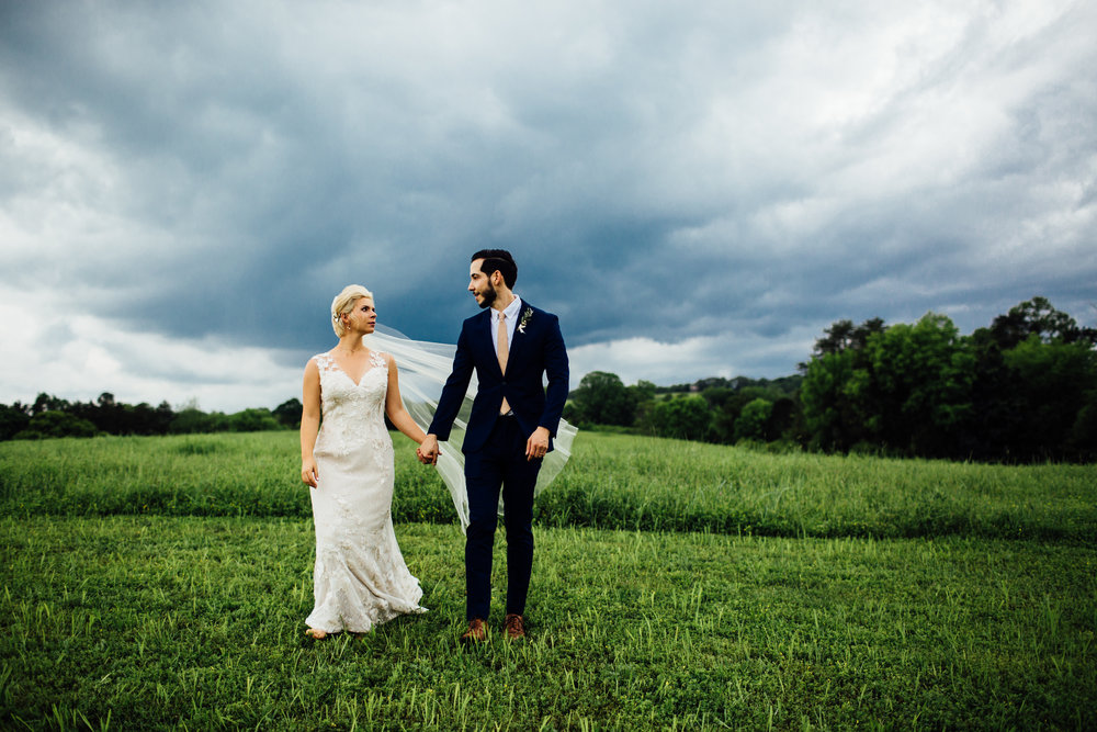 stormy bride and groom holding hands