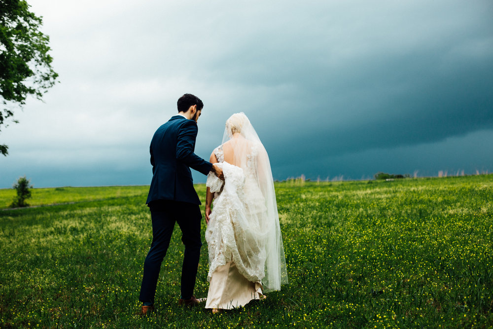 stormy sky bride and groom walking up hill