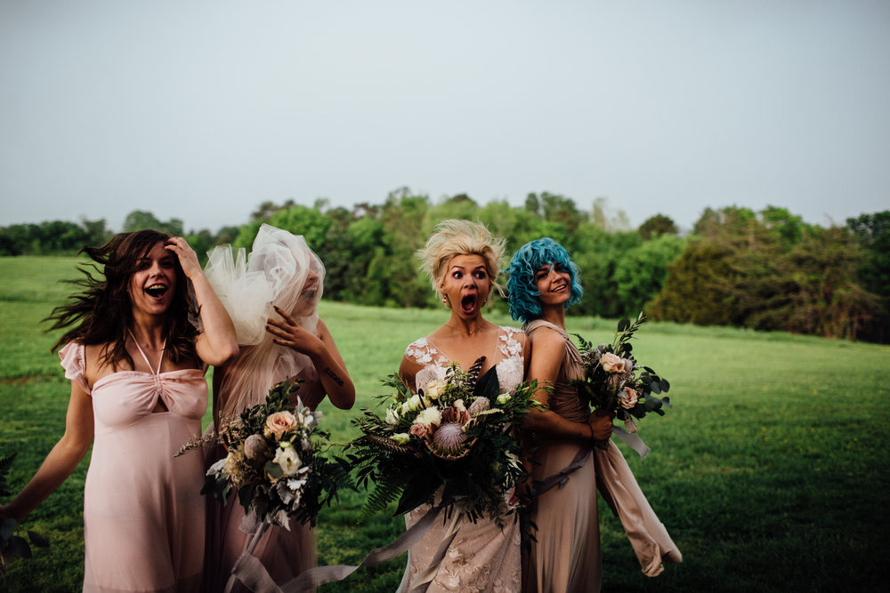 bride and bridesmaids surprised by the incoming windy storm