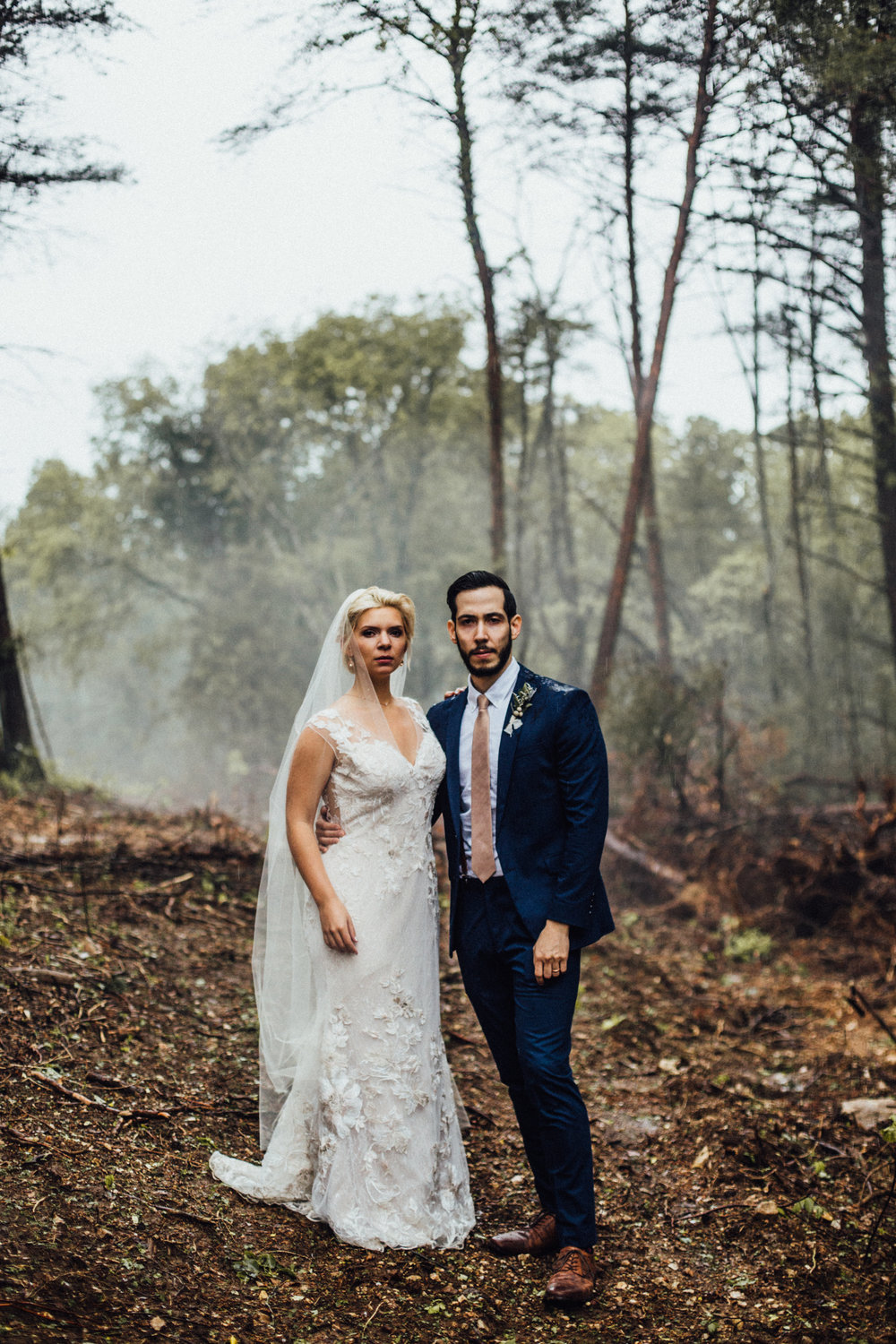 bride and groom serious foggy portrait after rain in the woods