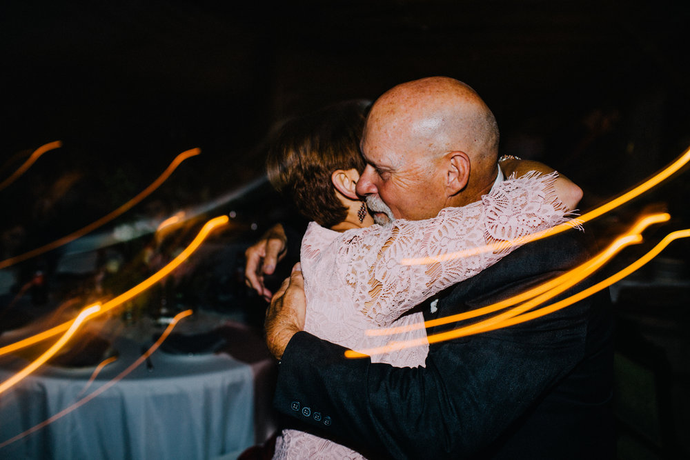 mother and father of the bride embracing at reception