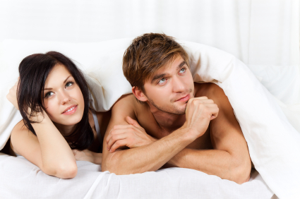 Man and woman in bed looking off into space and fantasizing