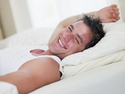man-lying-in-bed-laughing.jpg