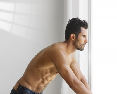 Attractive and muscular shirtless man looking out a window