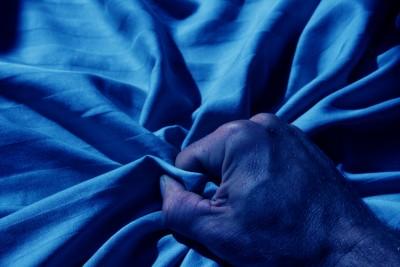 Man's hand grabbing bed sheet
