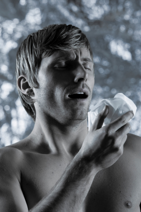 Muscular shirtless man sneezing