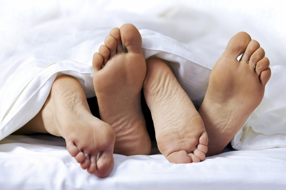 A couple's feet sticking out from under the sheets while having sex