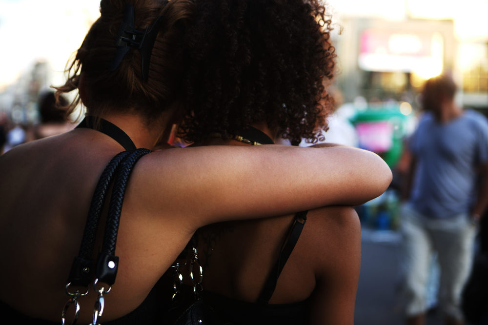 Lesbian couple with their arms around one another