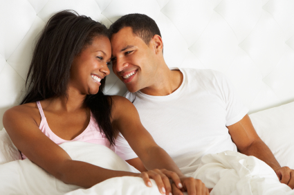 couple-smiling-and-relaxing-in-bed-pajamas.jpg