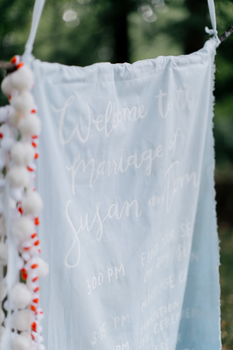 hello, bird. white brush calligraphy on hand-dyed fabric ceremony program // poms crafted by the couple  // photo courtesy of Emily Wren Photography