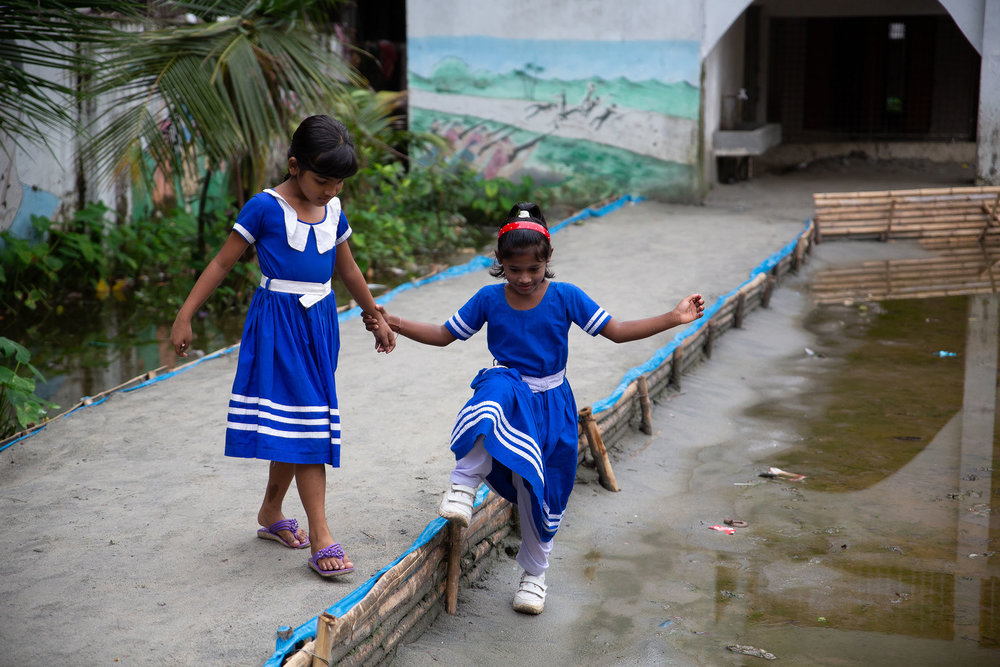 Girls help one another through flooded school courtyard, Nuru Chala Primary School.
