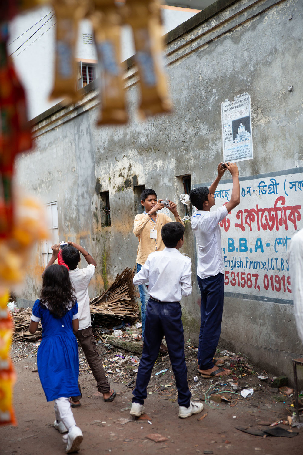 Students taking pictures for the Lesson 1 scavenger hunt, Nuru Chala neighborhood of Dhaka.