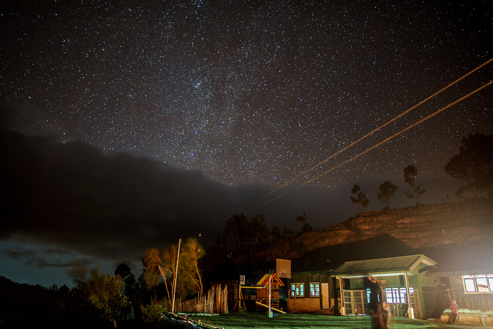 Domolpos Village at night, with the Milky Way vaguely visible behind the clouds.